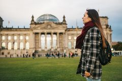 A tourist girl with a backpack next to the building called the Reichstag in Berlin in Germany. Sightseeing, tourism. Travel around Europe Stock Images