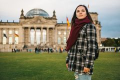 A tourist girl with a backpack next to the building called the Reichstag in Berlin in Germany. Sightseeing, tourism. Travel around Europe Royalty Free Stock Photography
