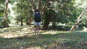 Tourist girl with backpack is walking along tropical forest. Female feet stepping at hill at the wood. Young woman going Stock Images