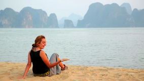 Tourist girl at beach,limestone view of halong bay,vietnam stock footage