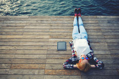 Tourist girl in bright glasses lying on jetty by river Stock Photos