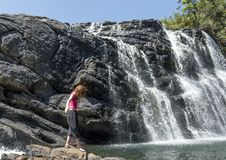 Tourist girl carefully walking near the Baker`s falls. At the national park in Sri Lanka stock photography