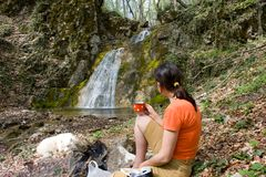Tourist girl with cup of tea near of waterfall Royalty Free Stock Image
