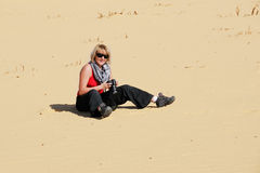 Tourist girl in desert. Young tourist girl with photo camera sits on a sand in the Sahara desert. Extreme travel concept Stock Images