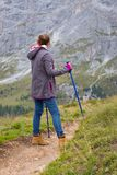 Tourist girl at the Dolomites. Girl hiker walking along the trail at the mountains Dolomites, Italy royalty free stock images