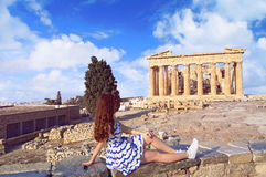 Tourist girl dressed in Greece flag colors looking at Parthenon Stock Photo