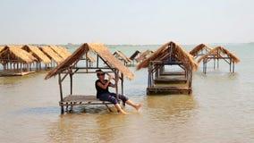 Tourist girl enjoying bungalows inside river stock video footage