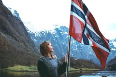 Tourist girl with flag of Norway enjoys beautiful view of fjord and mountains Stock Images