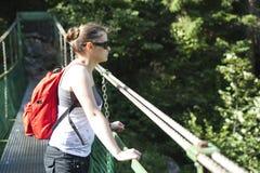 Tourist girl on hanging bridge royalty free stock photography