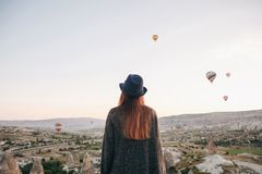 A tourist girl in a hat admires hot air balloons flying in the sky over Cappadocia in Turkey. Impressive sight. Tourism royalty free stock image