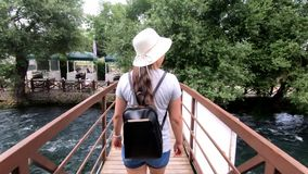 Tourist girl in hat and with a backpack is on a wooden bridge over the river, around a lot of greenery and trees stock video