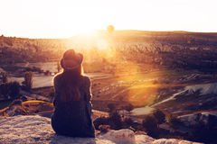 A tourist girl in a hat sits on a mountain and looks at the sunrise and balloons in Cappadocia. Tourism, sightseeing. A tourist girl in a hat sits on a mountain Stock Image