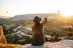 A tourist girl in a hat sits on a mountain and looks at the sunrise and balloons in Cappadocia. Tourism, sightseeing Stock Photo