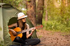 Tourist girl in hat sits in tent and playing guitar concept. Tourism rest on nature. royalty free stock photography
