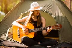 Tourist girl in hat sits in tent and playing guitar concept. Tourism rest on nature. royalty free stock images