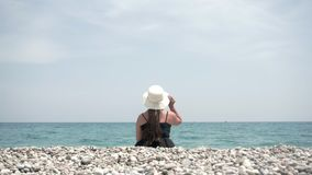 A tourist girl in a hat with wide edges sits on the shore of the warm sea and admires the beautiful view of the water stock video footage