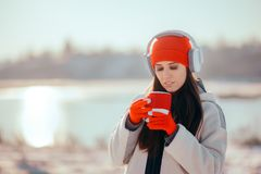 Winter Woman Drinking Hot Beverage Listening to Music. Tourist Girl with headphones relaxing outdoor holding coffee drink royalty free stock photo