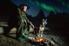 Tourist girl with her dog around campfire at misty landscape night stars and aurora borealis Royalty Free Stock Photos