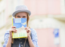 Tourist girl hiding behind map while standing on city street Stock Photos
