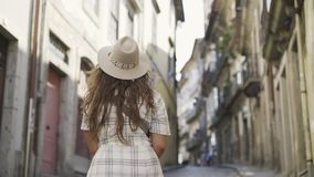 Tourist girl in history centre of Porto. Woman walking on street of ancient town in sunny day. Following from the back girl in dress and hat at blurred stock video