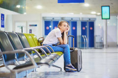 Tourist girl in international airport, waiting for her flight, looking upset. Beautiful young tourist girl with backpack and carry on luggage in international Stock Photo