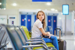 Tourist girl in international airport, waiting for her flight, looking upset stock photography