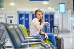 Tourist girl in international airport, waiting for her flight, looking upset. Beautiful young tourist girl with backpack and carry on luggage in international Stock Photography