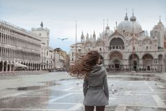 Tourist girl with long blowing hair in Piazza San Marco in front Royalty Free Stock Photos