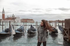 Tourist girl with long blowing hair on the pier, near the gondol Royalty Free Stock Photography
