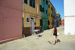 Tourist girl looking at Venice Burano colorful house, afternoon in a little street of Burano, Venice, Italy summer 2016 Royalty Free Stock Photography