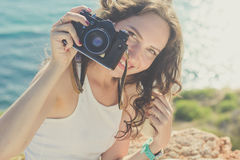 Tourist girl making photo by old camera on mountain top Royalty Free Stock Image