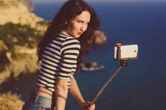 Tourist girl making selfie photo with stick on mountain top Royalty Free Stock Image