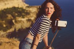 Tourist girl making selfie photo with stick on mountain top Stock Images