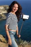 Tourist girl making selfie photo with stick on mountain top Stock Photos