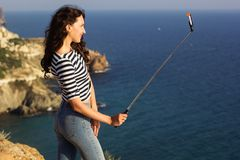 Tourist girl making selfie photo with stick on mountain top Royalty Free Stock Images