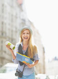 Tourist girl with map and cup of hot beverage on city street Royalty Free Stock Photography