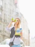Tourist girl with map drinking hot beverage on city street Royalty Free Stock Photos