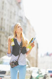 Tourist girl with map looking for something on city street Stock Photo
