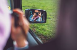 Tourist girl in an open window of a car taking photography click on retro vintage photo camera, photographer looking on reflection royalty free stock image