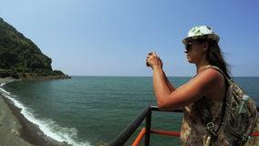 Tourist girl photographing sea. Girl tourist on observation deck photographs coast stock video footage