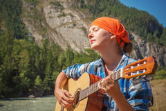 Tourist girl playing a guitar Royalty Free Stock Photography