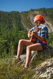 Tourist girl playing a guitar Stock Images