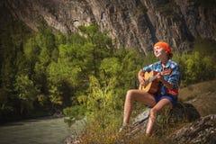 Tourist girl playing a guitar Stock Photography