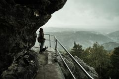 Tourist girl with a puppy dog looking at the misty fog mountains from viewpoint of Bastei in Saxon Switzerland, Germany. To the mountains at sunrise in the stock photos