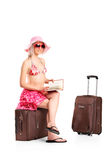 Tourist girl reading a book seated on a luggage Royalty Free Stock Photos