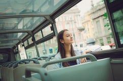 Tourist girl rides on a tour bus royalty free stock photography