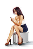 Tourist girl seated on suitcase Stock Photography