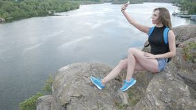 A tourist girl sits on a rock. And makes a selfie stock footage