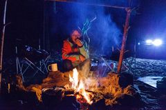 Tourist girl sitting by the campfire at night. Royalty Free Stock Image