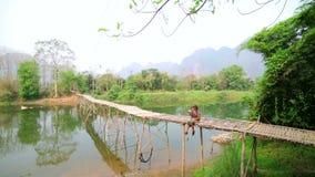 Tourist girl sitting and drinking coffee on bamboo bridge, laos